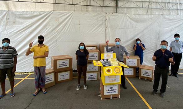 Dr Gilbert Tan (depan, kanan) bersama kakitangan Poliklinik SingHealth (SHP) sumbang lebih 1,700 pakaian dan tuala baru kepada pekerja asing di sini. - Foto POLIKLINIK SINGHEALTH